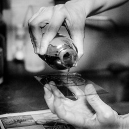 Pouring collodion solution - 1.5-2% Collodion in ether-ethanol mixture - onto the plate and tilting it to distribute the solution evenly