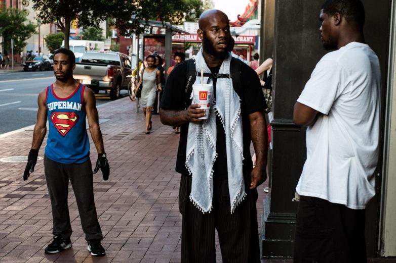 A street dancer awaits his cue in Chinatown. Washington D.C, USA.