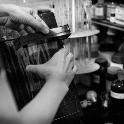 Flemming gently rests his collodion coated glass into the holder, and dunks it into the silver nitrate container.