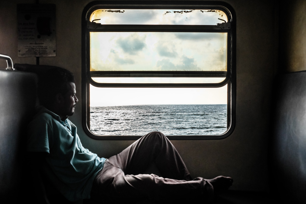 A passenger on the train looks out at the sea as the train chugs along the coast. Colombo, Sri Lanka.