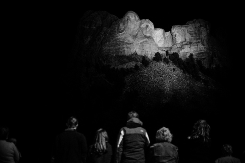 Visitors stand for the national anthem as Mount Rushmore is lit