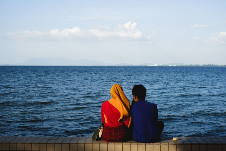 Locals enjoying each other's company by the Esplanade seaside. Georgetown, Penang.