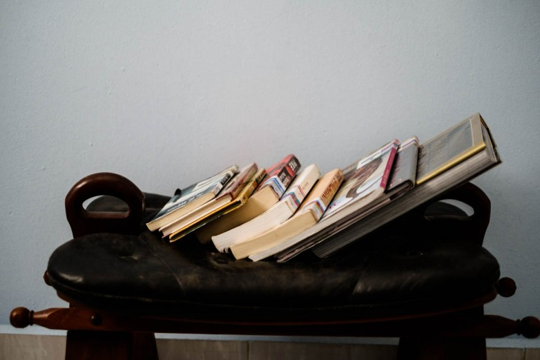 Library books rest on a foot stool in my room in Singapore