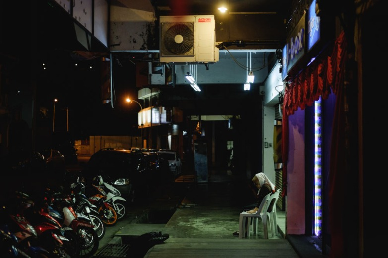 A young girl rests in the five foot way at night. Georgetown, Penang.