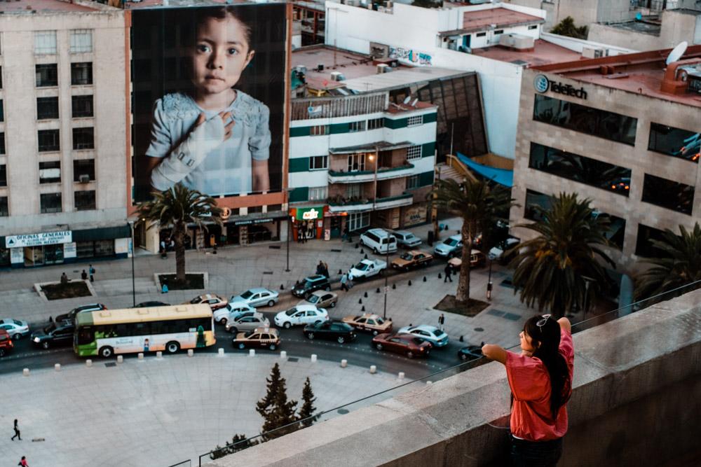 A child gazes out over the city on Monumento ala Revolucion. Mexico City, Mexico.
